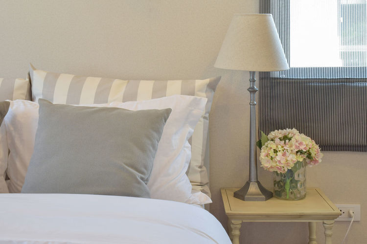 modern bedroom interior with green striped pillow on bed and decorative table lamp at home Flower Flowering Plant Furniture Plant Indoors  Pillow Vase No People Domestic Room Home Interior Comfortable Bed Nature Bedroom Electric Lamp Home Showcase Interior Lighting Equipment Night Table White Color Seat Flower Arrangement Bouquet Cozy Flower Head Side Table