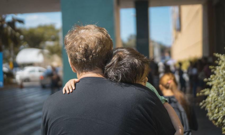 Rear view of couple walking on street in city