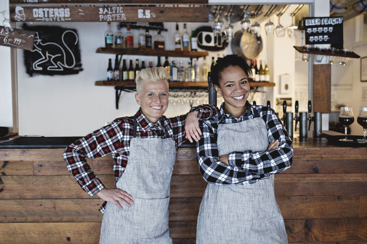 Portrait of smiling female bartenders standing against bar counter