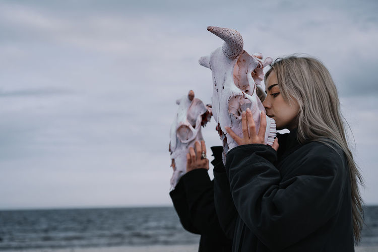 Woman holding cow skull by the sea against cloudy sky