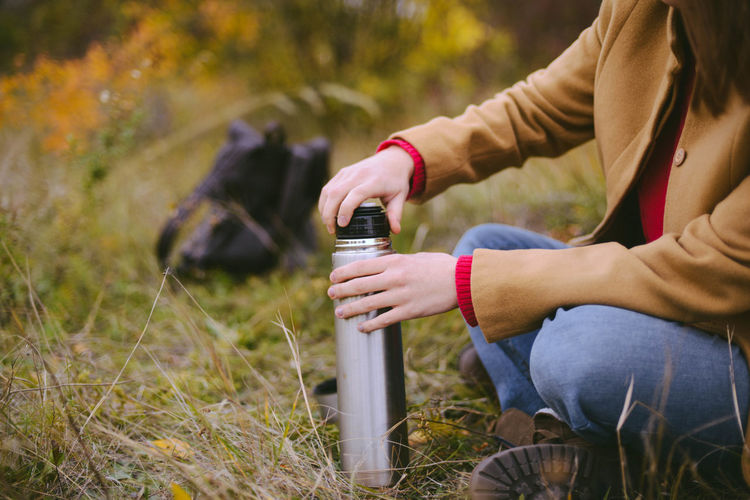 Low section of woman holding insulated drink container while sitting on field during autumn