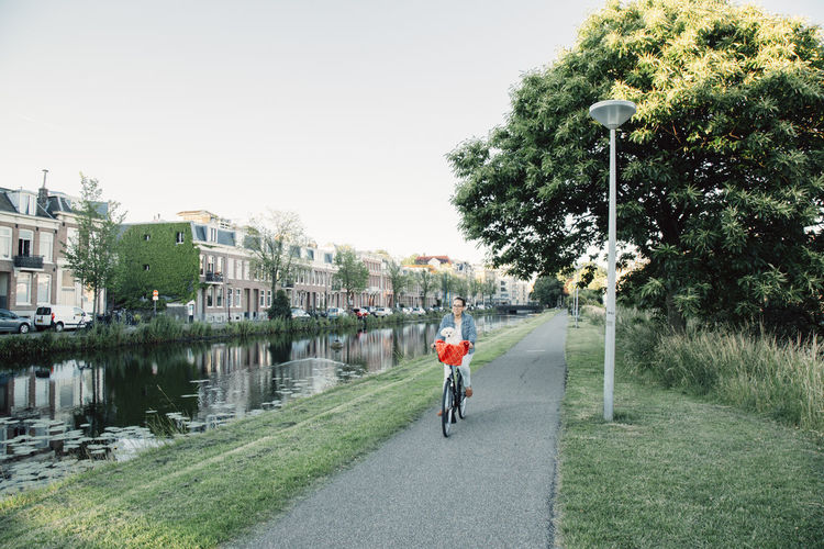 Woman with dog on bicycle basket next to Amsterdam canal. Amsterdam Amsterdamcity Ams EyeEmNewHere Bike Path Amsterdam Oost Amsterdam Bikes Dog Dogslife Dogs Of EyeEm Dogstagram Summer Netherlands Amsterdam Canal Amsterdamse Grachten Rescue Dog Rescuedog Cycling Helmet Water City Tree Bicycle Headwear Mountain Bike Men Cycling Sky Bicycle Lane Canal Riding Biker Stories From The City Summer Exploratorium