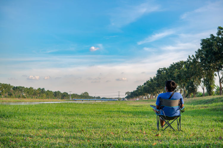 Rear view of man sitting on field against sky