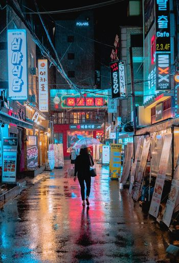 Rear view of woman carrying umbrella in city at night during rain