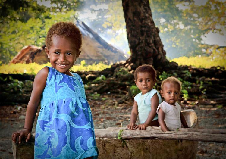 I took this picture while along the beach of Pentecoste Island, Vanuatu. I saw these three children playing on a hand-made canoe. This beautiful girl is called Genoveve. Blue Childhood Children Children's Portraits Enjoyment Happiness Inocence  Pentecost Island Sister Smiling The Portraitist - 2017 EyeEm Awards Togetherness Vacations