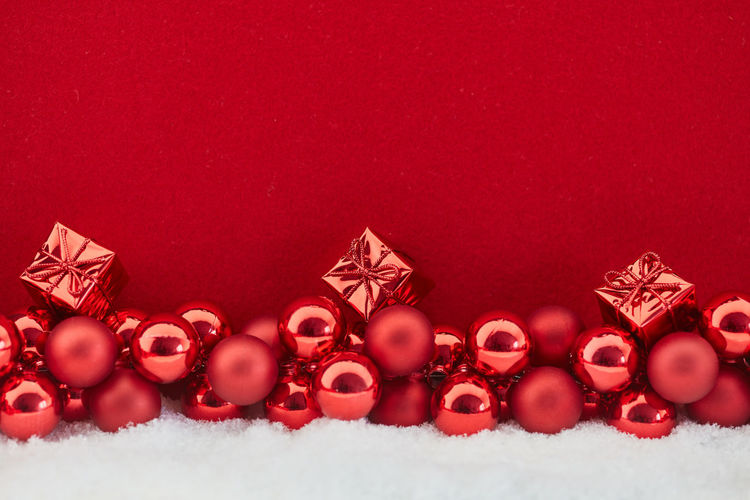 Red Christmas Baubles And Gifts On Snow Against Wall