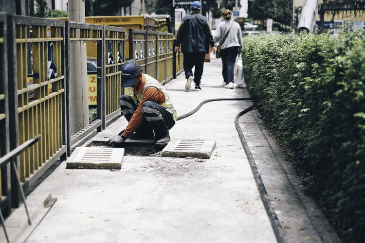 A worker maintaining a sewer Adult Architecture BYOPaper! Day Full Length Maintenance Maintenance Engineer Maintenance Work Men Outdoors People Real People Street Streetphotography The Street Photographer - 2017 EyeEm Awards Working