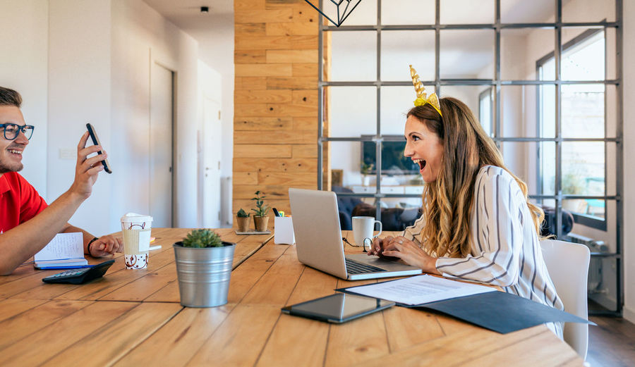 Laughing businesswoman and businessman talking at office