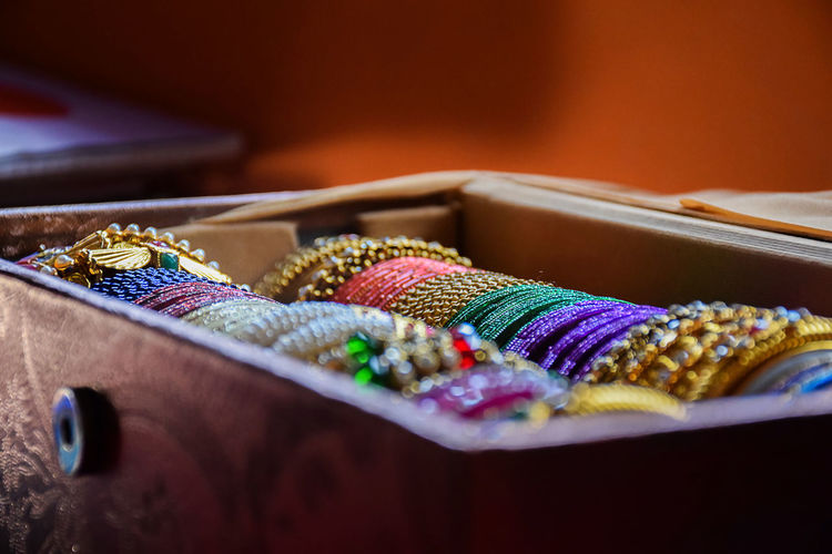 Close-up of multi colored bangles in container on table
