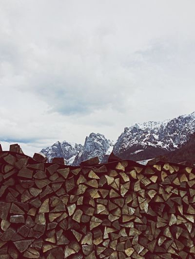 Stack of firewood against cloudy sky