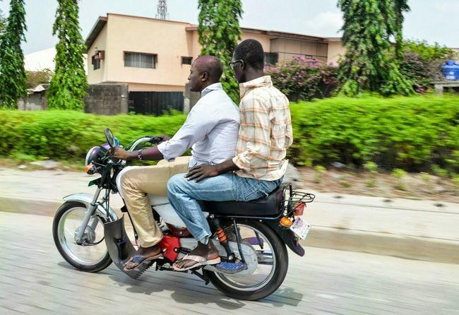 Men Riding an Okada Motor Bike in Lagos, Nigeria