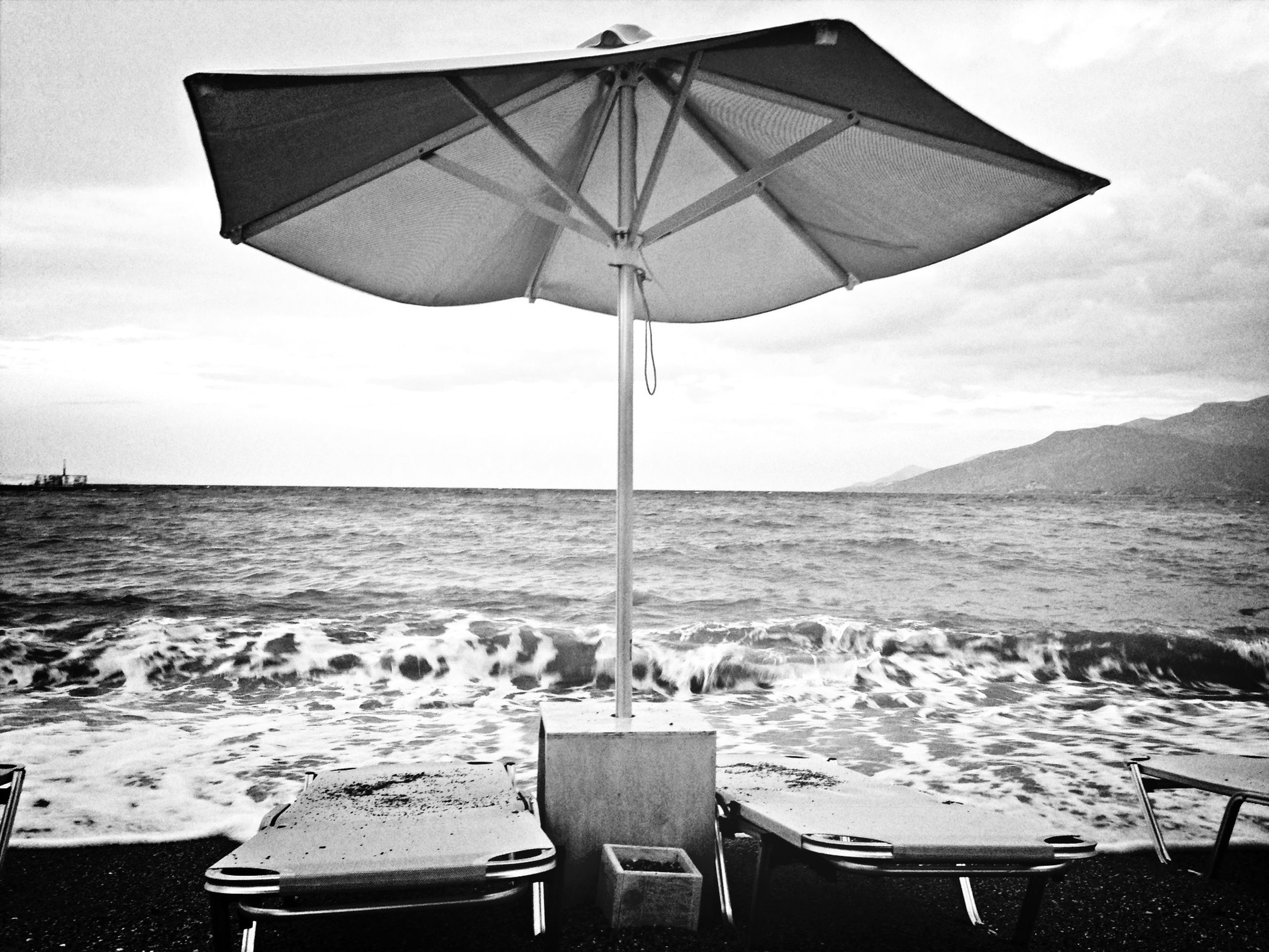 sea, water, sky, beach, horizon over water, beach umbrella, shore, tranquility, scenics, tranquil scene, sunshade, nautical vessel, nature, parasol, cloud - sky, flag, day, building exterior, outdoors, built structure