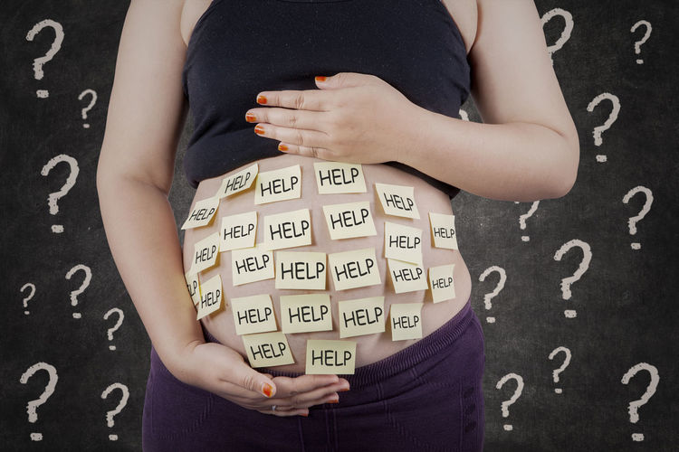 Midsection Of Pregnant Woman With Help Text On Sticky Notes Stuck To Abdomen