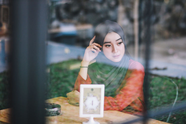 Young Woman Sitting In Cafe Seen Through Window