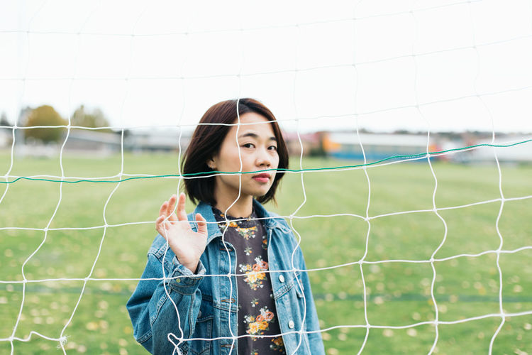 Portrait of woman seen through net while standing on sports field