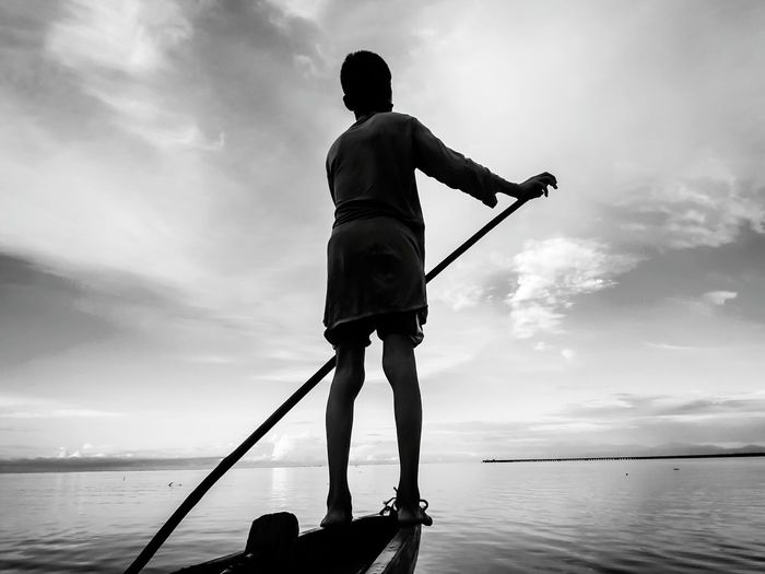 Rear view of boy on rowboat against sky