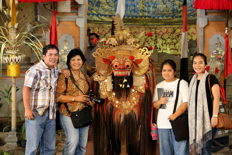 Portrait Of Family Standing By Dragon Decoration Against Temple