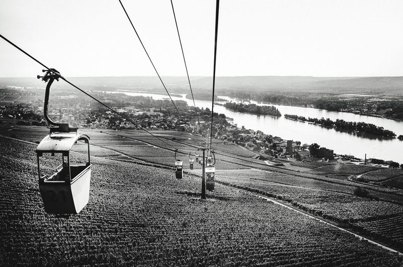 Overhead cable car on landscape against clear sky