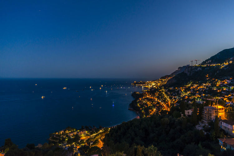 Illuminated city by sea against blue sky