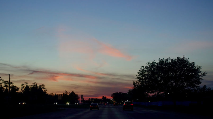 Silhouette trees by road against sky at sunset