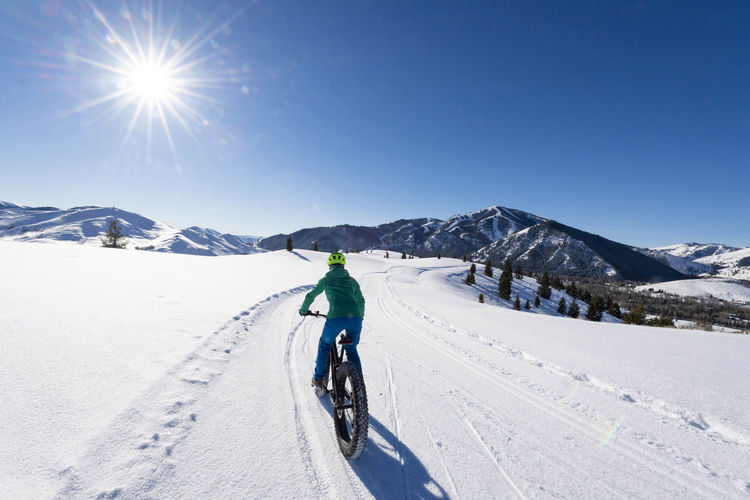 Man riding bicycle on snowcapped mountain against sky