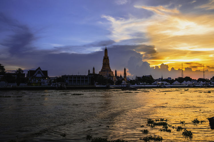 Wat Arun or Wat Arun is a temple on the west bank of the Chao Phraya River, Bangkok, Thailand. Architecture Building Building Exterior Built Structure City Cityscape Cloud - Sky Government Nature No People Outdoors River Sky Sunset Tourism Travel Travel Destinations Water Waterfront