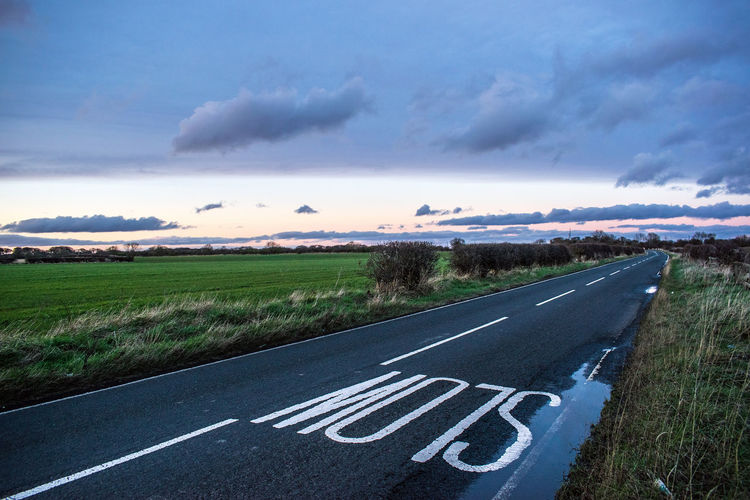 Cloud - Sky Day Diminishing Perspective Direction Dividing Line Empty Road Environment Field Grass Land Landscape Marking Nature No People Outdoors Road Road Marking Scenics - Nature Sign Sky Symbol The Way Forward Transportation