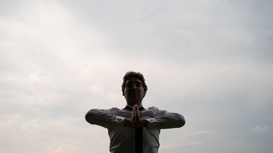 Low angle view of man with hands clasped standing against sky