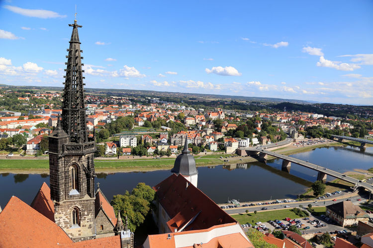 Meissen cathedral by elbe river against sky in town