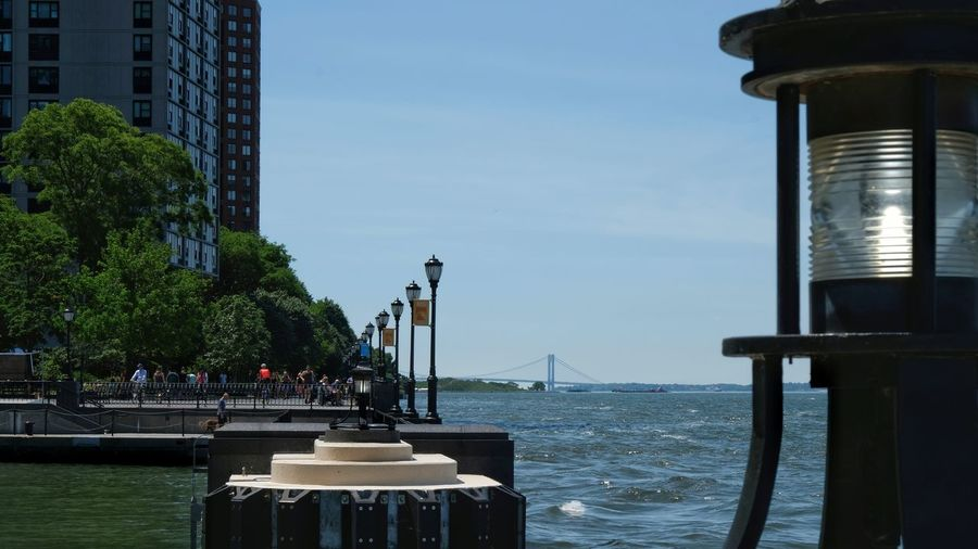 Looking into the harbor. Photography NYC Landscape People Wide Open Spaces Fuji Xt20 Fresnel Light Lampposts River Water Tree City Sea Sky Building Exterior Built Structure Cityscape Downtown