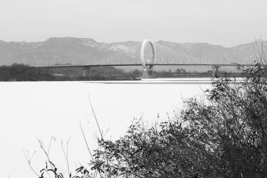 black and white image of snow-covered lake, Uiamho Lake in Chuncheon, Gangwondo, South Korea Black & White ChunCheon Cold Lake Cold Weather Gongjicheon Snow Land Uiamho Lake Winter Winter Landscape Architecture Beauty In Nature Black And White Blackandwhite Bridge - Man Made Structure Bw Clear Sky Cold Cold Temperature Connection Day Landscape Mountain Mountain Range Nature No People Outdoors River Scenics Sky Snow-covered Snow-covered Lake Suspension Bridge Tree Water Winter Lake Winter Land Winter Time