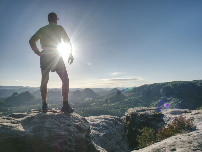 Man doing stretching exercise outdoors. extreme runner climbs the mountain top and see wide valley