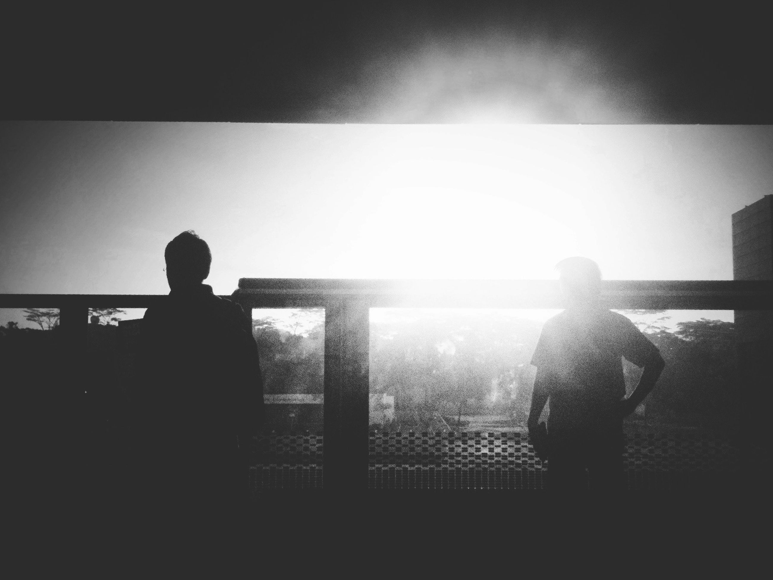 silhouette, indoors, rear view, lifestyles, standing, full length, leisure activity, men, togetherness, water, sea, sitting, person, side view, outline, sunlight, railing