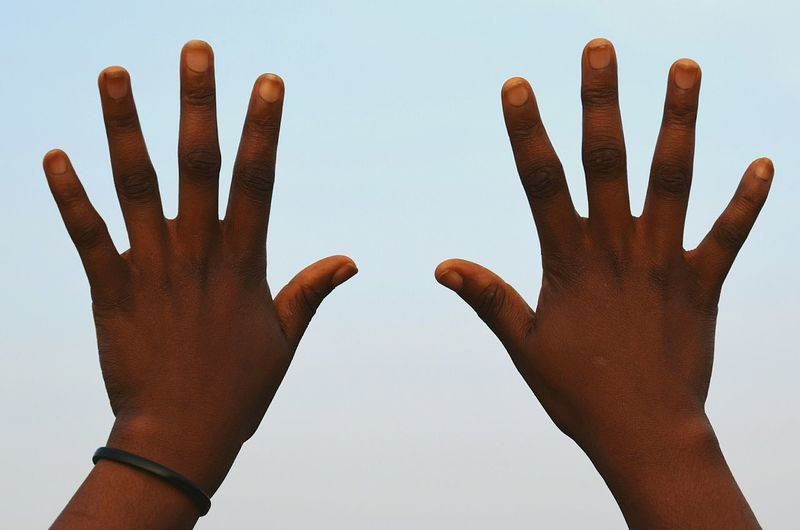 Close-up of hand showing stop gesture against clear sky