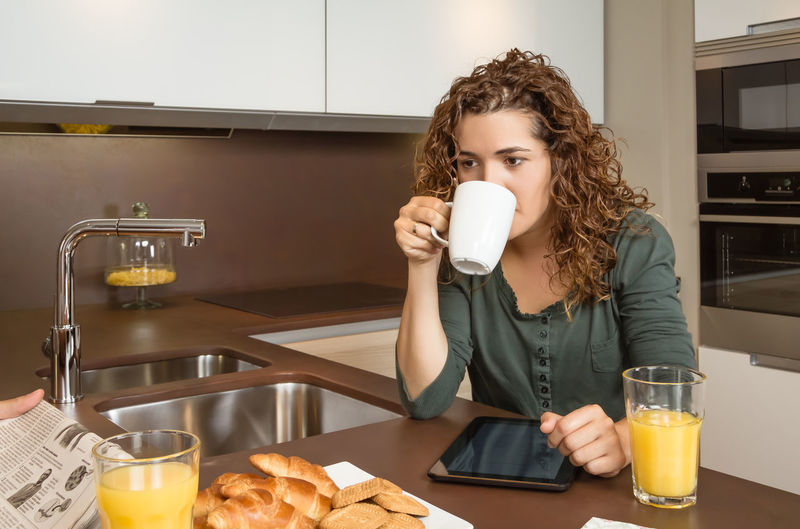 Tired young girl with cup of coffee at home breakfast while her husband reading news in the newspaper Family Fruit Girlfriend Thirties Relaxing Husband Boyfriend 30s Wife Relationship Adult Lifestyle Interior Love Cup Caucasian Healthy Two Coffee Glass Orange Girl Juice Meal Drink Together Young Woman Kitchen Man Indoors  Food Morning Technology Newspaper Digital Tablet News Read Problems Bored Tired Serious Male Home People Female Couple Breakfast