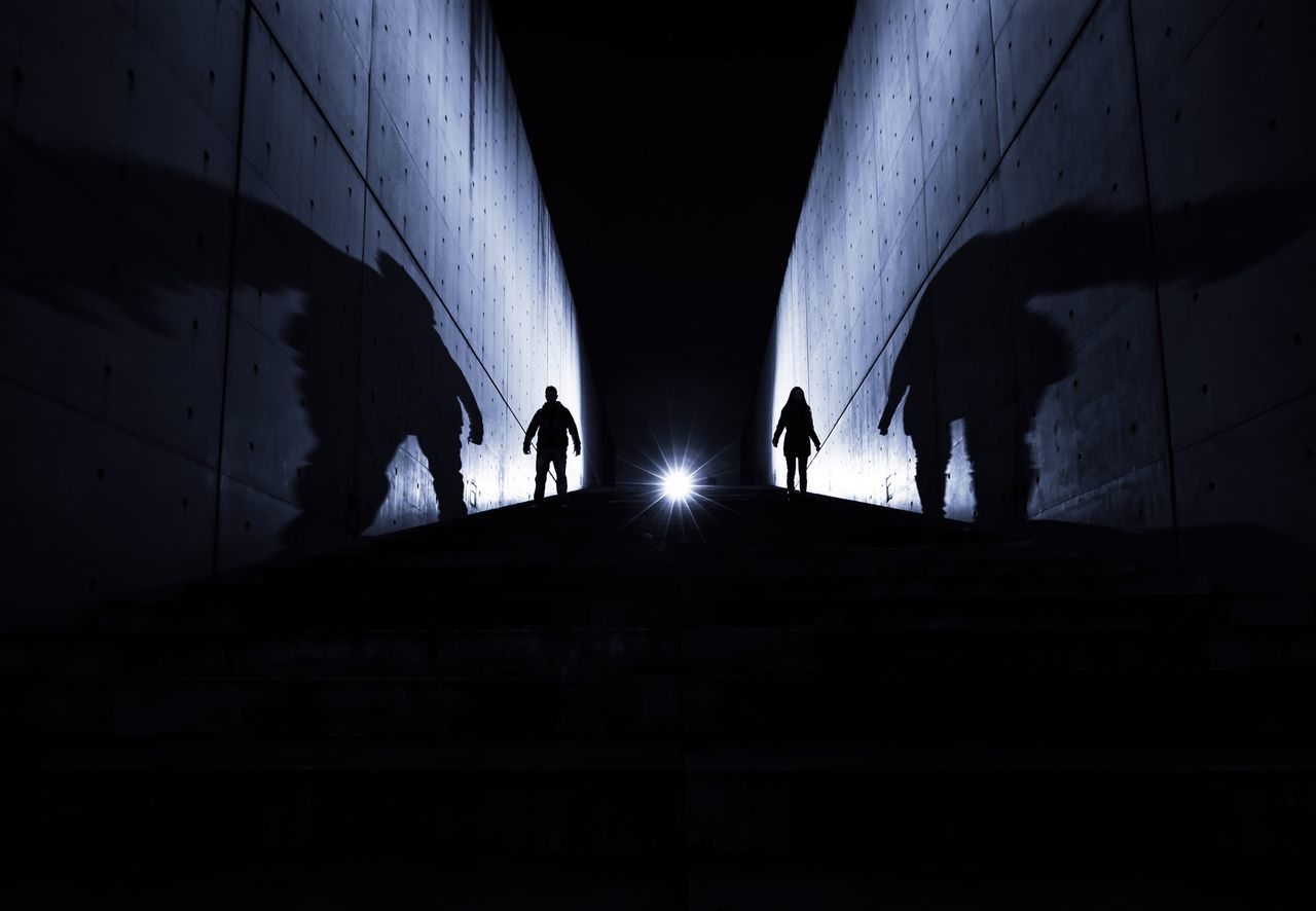 Low angle view of silhouette people on footpath amidst walls at night