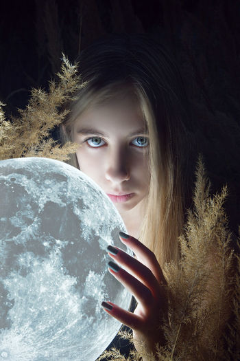 Digital Composite Image Of Young Woman Holding Moon In Darkroom
