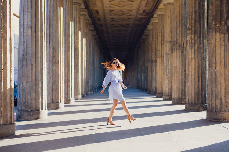 Smiling young woman walking amidst columns