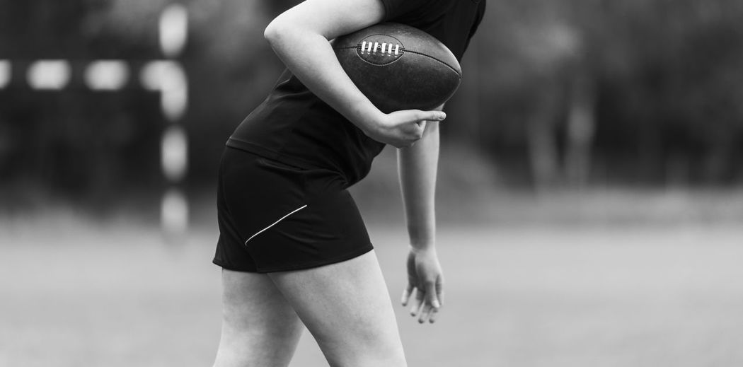 Midsection of woman holding american football while standing outdoors