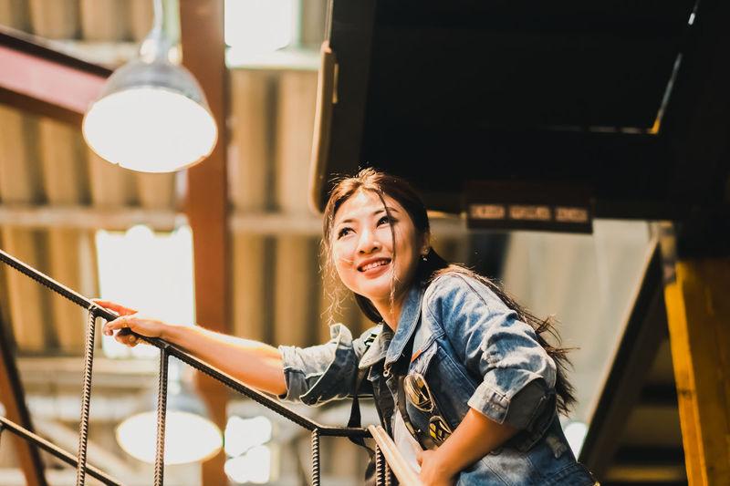 Smiling woman standing under illuminated pendant light
