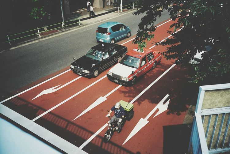 High Angle View Of Cars And Motorcycle On Street In City