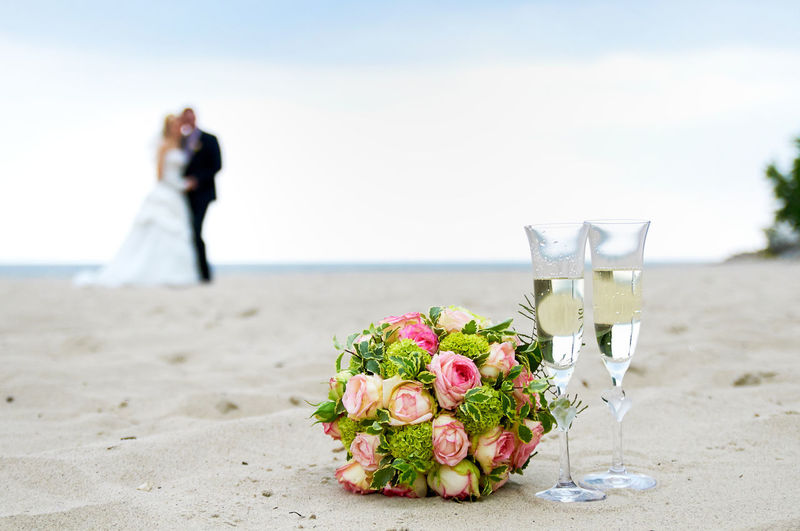 Close-up of various flowers on beach table against sea