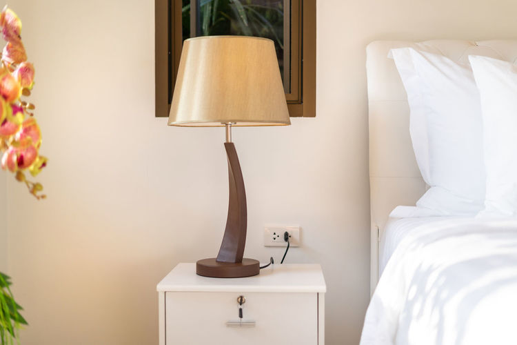 Electric lamp on bed at home