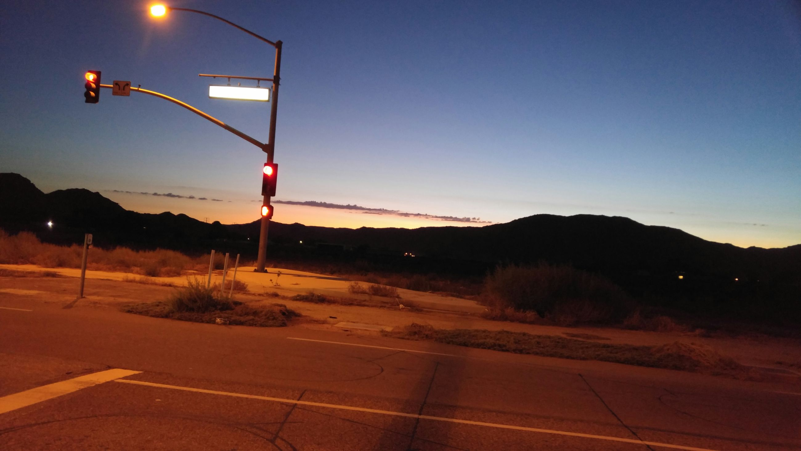 road, transportation, mountain, road sign, road marking, clear sky, sky, street light, red, landscape, street, the way forward, blue, mountain range, illuminated, guidance, copy space, outdoors, empty, dusk