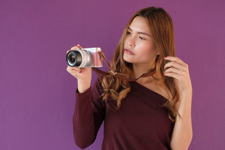 Young woman photographing while standing against purple wall