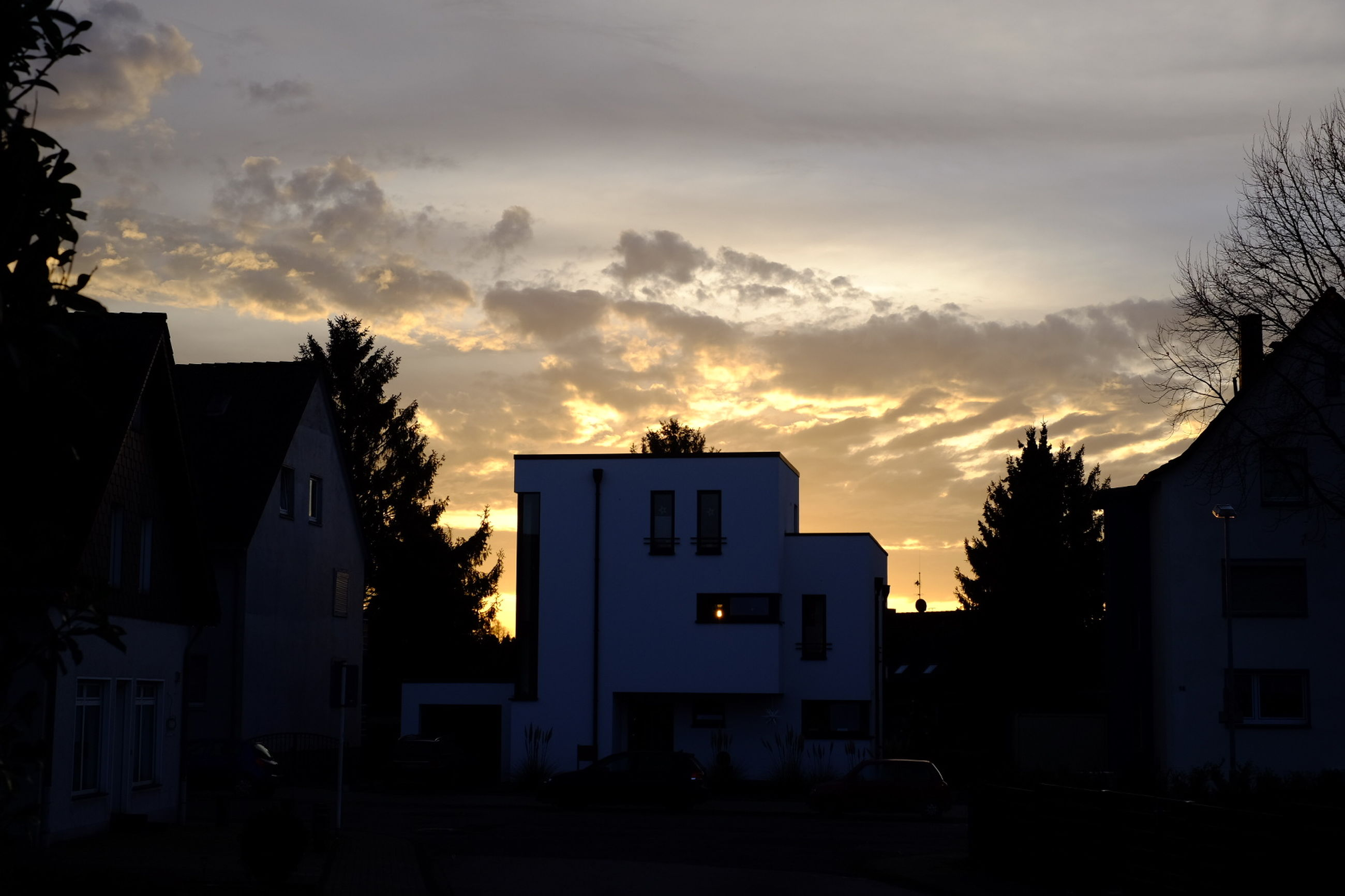 building exterior, sunset, architecture, built structure, silhouette, sky, cloud - sky, house, residential structure, residential building, cloud, tree, building, dusk, low angle view, cloudy, city, orange color, outdoors, dark