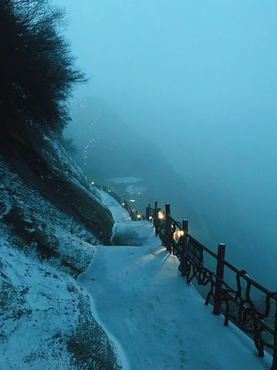 Snow covered pathway on mountain