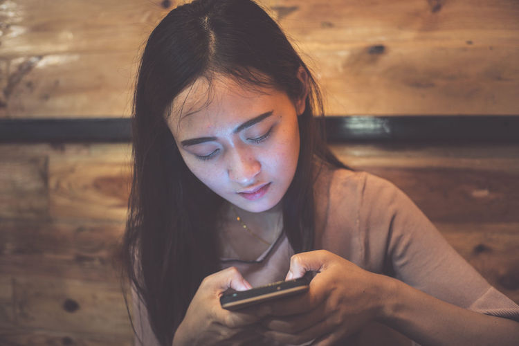 Close-up of young woman using mobile phone at restaurant