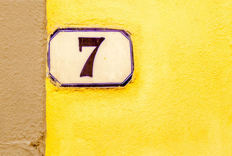 Close-up of number 7 on yellow wall