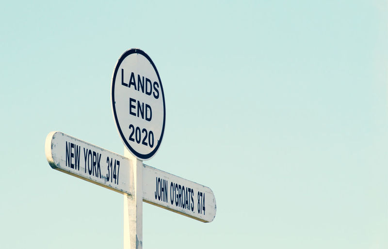 Low angle view of road sign against clear sky